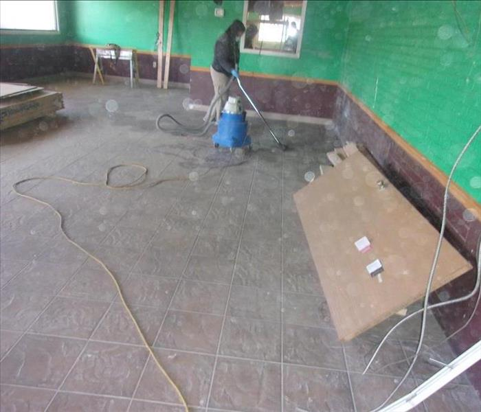The floor is clean of blown-in insulation. A single SERVPRO crew member vacuums the floor of remaining insulation.