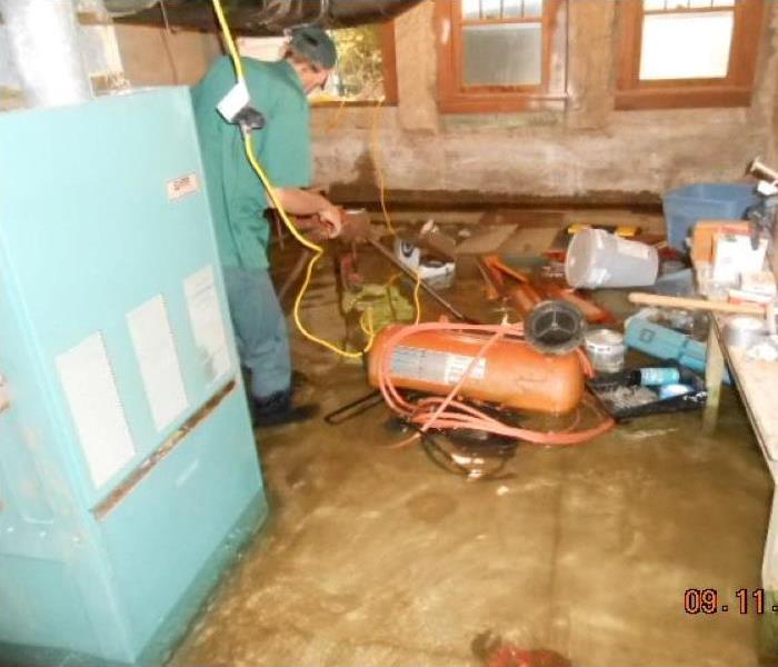 A basement is flooded with aproximately 10 inches of water. Contents float in the water. A SERVRPRO man is extracting it.