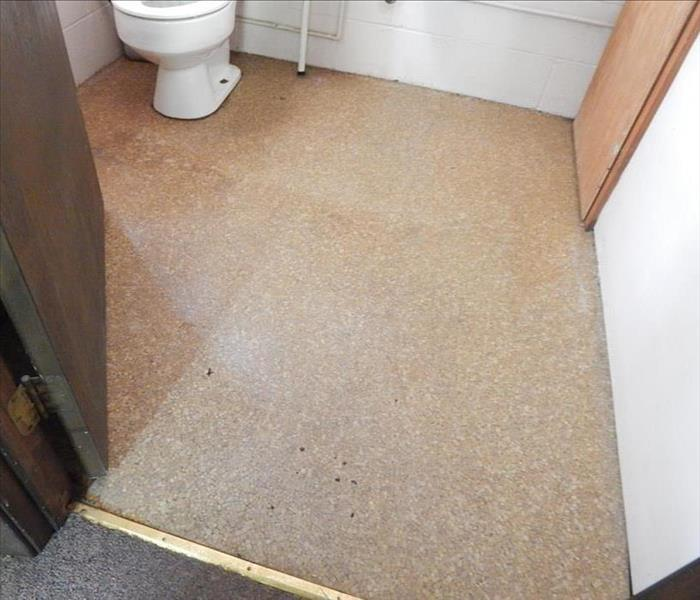 An orange tile bathroom floor clear of water and is dry. A white toilet is seen in the background.