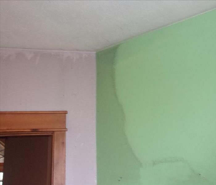 A green wall and a pink wall, covered with soot. Some of the soot has been wiped off to reveal the bright green underneath.