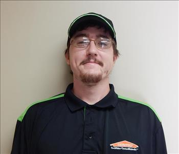 A man with a SERVPRO hat and uniform, brown hair, and glasses.