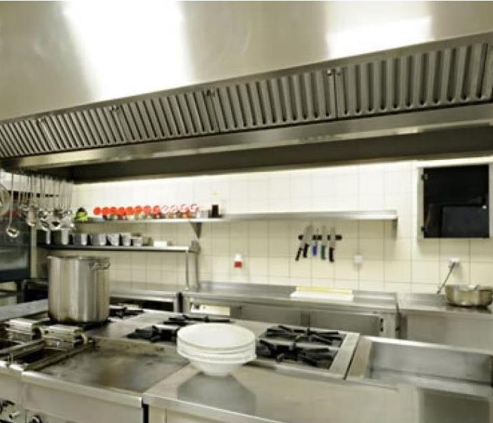 A large stainless steel restaurant kitchen stove with an overhead exhaust.