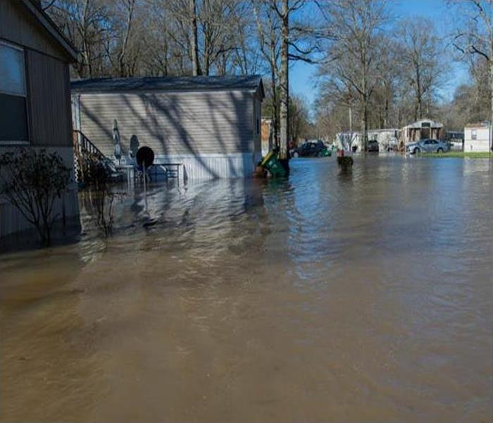 A trailer park sits in brown, murky flood waters.