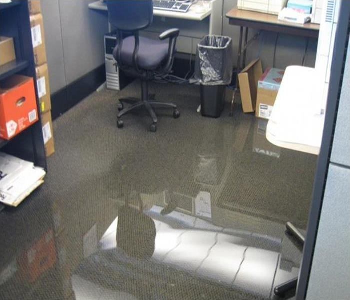 An office cubicle with standing water, soaked carpeting, and boxes and furniture sitting in the puddle of water.