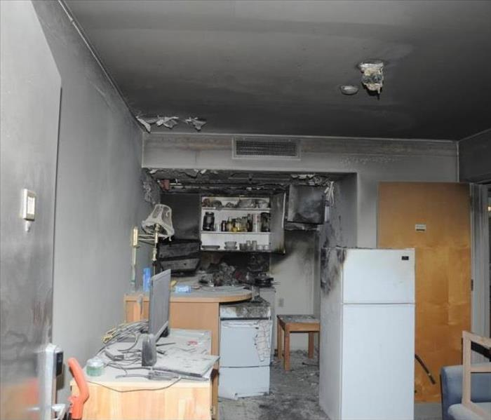 A kitchen with heavy soot damage on the walls and contents.